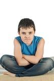Pojken sitter på en vit bakgrund royaltyfri fotografi