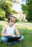 Pojken sitter på gräset i hörlurar med din minnestavla Arkivfoton