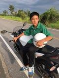 Pojken sitter på mopeden Royaltyfri Bild