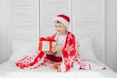 Pojken sitter på sängen och innehavet en ask med en gåva Royaltyfri Fotografi