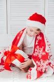 Pojken sitter på sängen och innehavet en ask med en gåva Fotografering för Bildbyråer