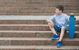 Pojken sitter på trappan, med sportar stiger ombord i hans händer royaltyfri bild