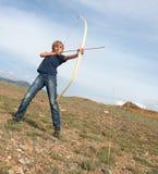 Pojken skjuter en bow på ett mål Arkivfoton