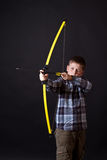 Pojken skjuter en pilbåge Arkivfoton