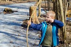 Pojken skjuter en pilbåge Royaltyfria Bilder
