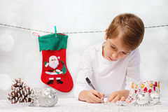 Pojken skrivar ett brev till Santa Claus Royaltyfria Bilder