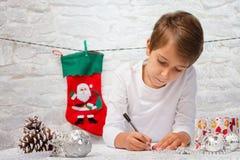 Pojken skrivar ett brev till Santa Claus Royaltyfri Fotografi