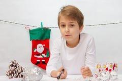 Pojken skrivar ett brev till Santa Claus Arkivfoto