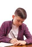 Pojken skriver något i anteckningsbok Arkivbilder