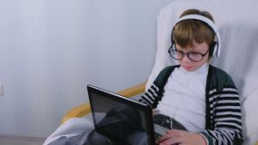 Pojken skriver och skriver ett meddelande p? b?rbara datorn i h?rlurar och exponeringsglas som sitter i f?t?lj arkivfilmer