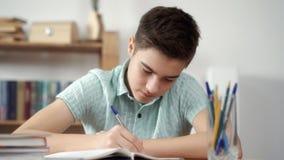 Pojken skriver och gör kurserna Royaltyfria Foton