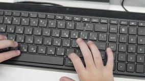 Pojken skriver på ett tangentbord från en dator stock video