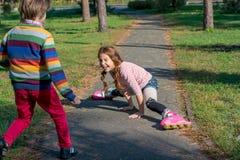 Pojken skynda sig för att hjälpa flickan, som avverkar som rullar på rullar Royaltyfria Foton