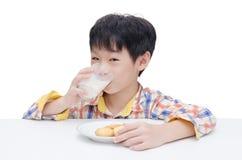 Pojken som äter kakor med, mjölkar royaltyfri foto