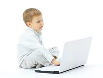 Pojken som använder bärbara datorn Fotografering för Bildbyråer