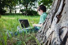 Pojken som använder hans utomhus- bärbar dator parkerar in, på gräs Royaltyfri Foto