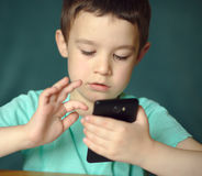 Pojken som använder minnestavlan, skjuter inomhus Royaltyfria Foton