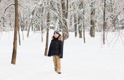 Pojken som går i ett snöig, parkerar på en solig dag Arkivfoto
