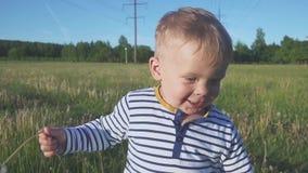 Pojken som går med en vit maskrosblomma i hans hand arkivfilmer