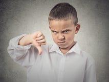 Pojken som ger tummar gör en gest ner Arkivbilder
