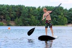 Pojken som har gyckel med, står upp skoveln på sjön royaltyfria foton