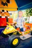 Pojken som kör bilen i amusemant, parkerar royaltyfri fotografi