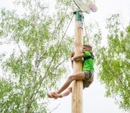 Pojken som klättras till överkanten av en trästolpe Royaltyfria Bilder