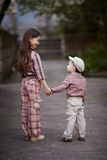 Pojken som kramar den gulliga systern och, ser upp Arkivbild