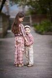 Pojken som kramar den gulliga systern och, ser upp Royaltyfri Fotografi
