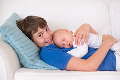 Pojken som rymmer hans nyfött, behandla som ett barn brodern Arkivfoton