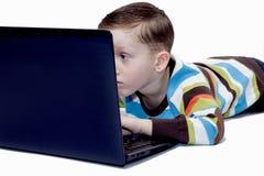 Pojke som leker med en bärbar dator Fotografering för Bildbyråer