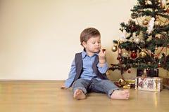 Pojken som ser jul, klumpa ihop sig framme av julträd Arkivfoton