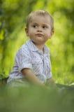 Pojken som sitts i gräsplan, parkerar Royaltyfria Foton