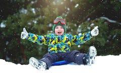 Pojken som sledding i en utomhus- vintergyckel för snöig skog för jul, semestrar arkivfoto