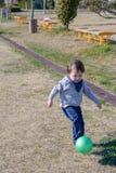 Pojken som sparkar bollen på, parkerar Royaltyfri Fotografi