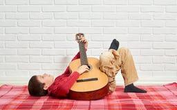 Pojken som spelar musik på gitarren som är iklädd en röd woolen tröja, ligger på en röd rutig filt, den vita tegelstenväggen på b Fotografering för Bildbyråer