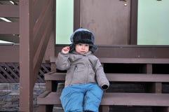 Pojken som två-år-är gammal i ett lock med öra-klaffar, sitter på en farstubro fotografering för bildbyråer