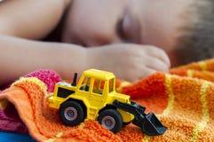 Pojken sover med bulldozerleksaken Royaltyfria Foton