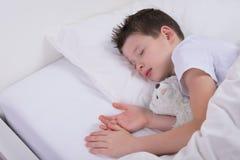 Pojken sover med hans favorit- leksak, i en vit säng royaltyfri fotografi