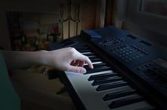Pojken spelar det elektroniska pianot royaltyfria foton