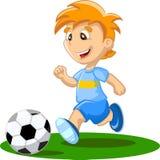 Pojken spelar fotboll Arkivfoto