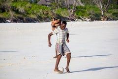Pojken spelar fotboll på en strand Royaltyfri Bild