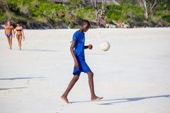 Pojken spelar fotboll på en strand Royaltyfria Foton