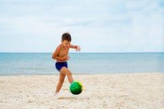 Pojken spelar fotboll på stranden royaltyfria foton