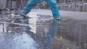 Pojken spelar i en pöl i regnet Han jublar i regnet Två-år-gammal pojkespring på trottoaren Begrepp lager videofilmer