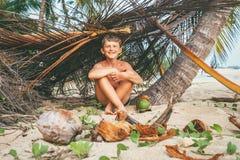 Pojken spelar i Robinzon på den tropiska stranden i koja av filialer royaltyfri fotografi