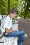 Pojken spelar i telefon i parkera Royaltyfri Foto