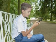Pojken spelar i telefon i parkera Arkivbilder