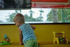 Pojken spelar leksaker i lekrum Arkivfoton