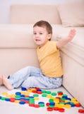 Pojken spelar med byggnadskvarter Arkivfoton